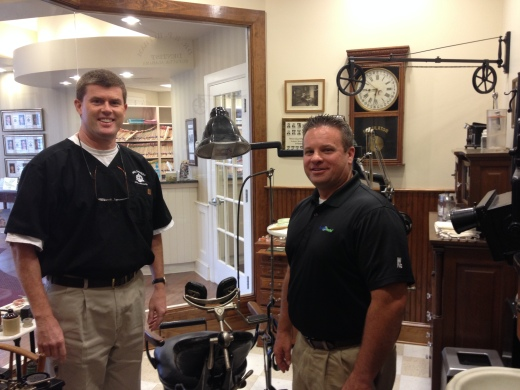 Dr. H. Paul Hufham III and his Friendly Benco Rep Doug Yeager standing in Dr. Hufham's mini-dental museum.