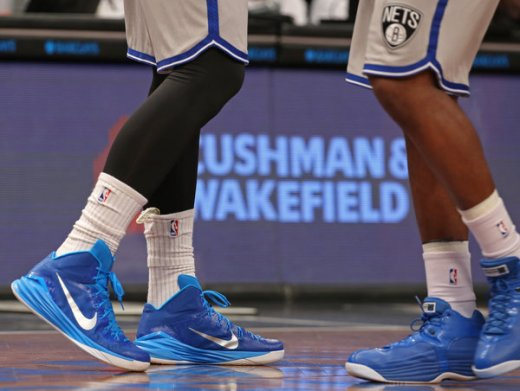 """The Nets' Mason Plumlee, left, tucks his mouthpiece inside one of his socks, which he acknowledged was """"not the most sanitary place in the world.""""  Credit Adam Hunger for The New York Times"""