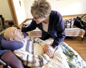 Photo courtesy: Agri-view. Angie Stone of HyLife oral care services greets George Schmidt, 88, before caring for his teeth at Huntington Place in Janesville.