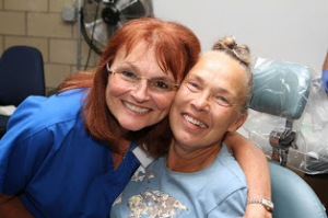 Chair of Dental Health and Program Director of Dental Hygiene, Kathleen Gazzola, at left, notes that in collaboration with the Rhode Island Oral Health Foundation they are hosting the fourth Rhode Island Mission of Mercy here at Community College of Rhode Island. She is shown at the 2013 Mission of Mercy with a patient.