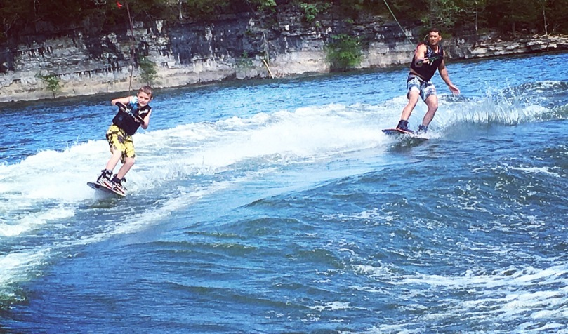 Image of Dr. Jackson wake boarding with son at Big Cedar.