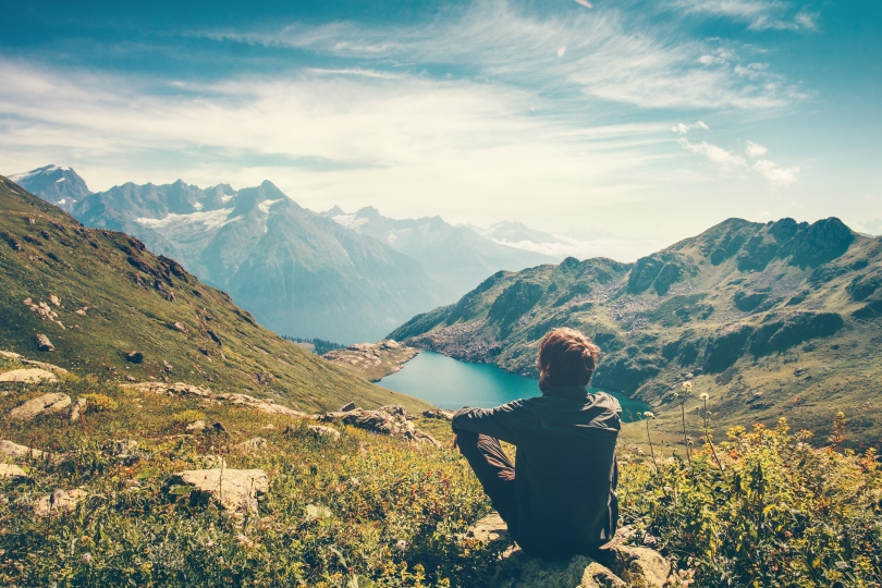 Image of a man chilling out in front of a beautiful landscape image.