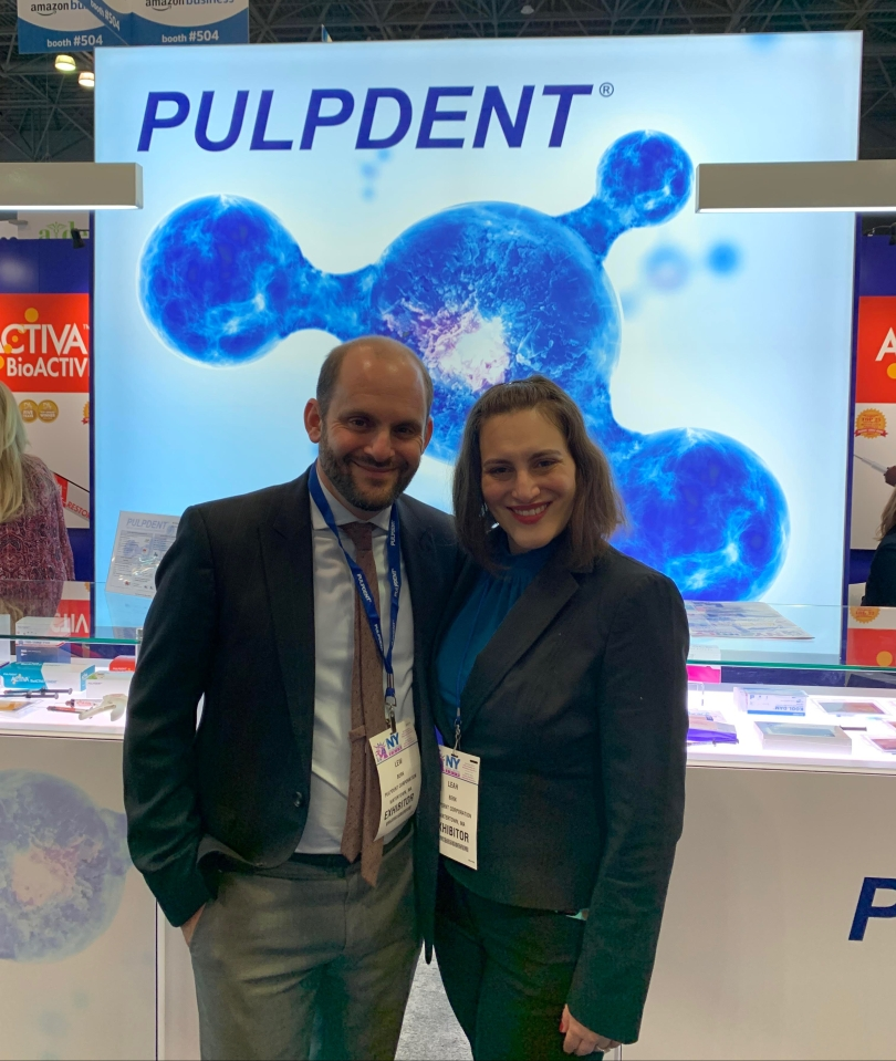 Lewis Berk and Leah Berk stand facing and smiling at the camera at a trade show. Behind them is a graphic representing an ion with the words Pulpdent right above it.